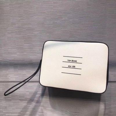 THOM BROWNE汤姆布朗新款男士手拿包 这款是今年专柜主打款 比以往的手包都更加能装东西 今年白色也很受欢迎 干干净净 时尚大方绝对是超级百搭的一款 TB-ASX